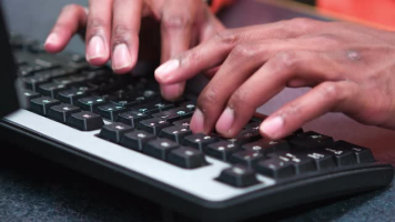Photo Illustration of hands typing on a keyboard