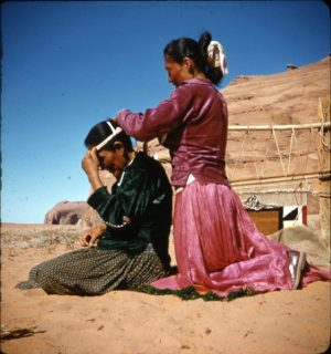 Navajo woman placing a headband on a Navajo man.
