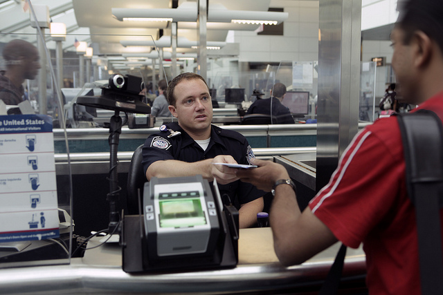 A CBP Officer processes an incoming passenger at the Newark International Airport. Photo by James Tourtellotte https://www.flickr.com/photos/cbpphotos/8468732156/in/photostream/
