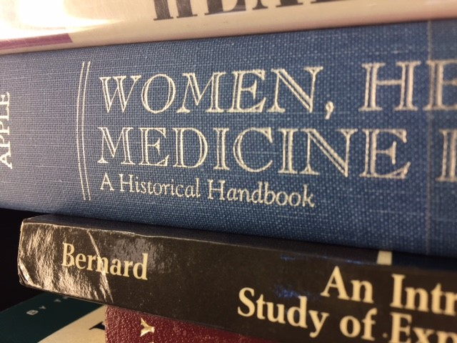 Stacked books with a book title Women, Medicine, A Historical Handbook
