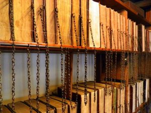 Books in medieval library with chains attaching them to shelves or each other.
