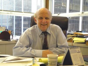 Floyd Abrams sitting at a desk with papers on it