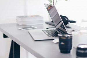black and white photo of a laptop sitting on an office desk Photo Credit by CC0 Pixabay