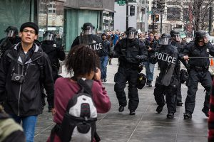 A photograph of of several police in riot gear advancing down a sidewalk during the Trump. Two officers on the right are looking off-camera with aggressive expressions. In the foreground, a tired-looking man with a camera around his neck walks away from the officers while a woman faces them with her camera raised.