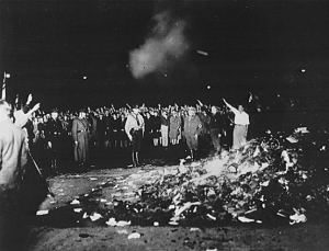 Thousands of books smoulder in a huge bonfire as Germans give the Nazi salute during the wave of book-burnings that spread throughout Germany. International News Photos. From the National Archives.