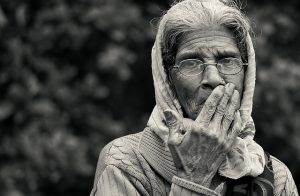 A black-and-white photograph of an elderly woman wearing a cardigan, glasses, and a scarf on her head. Her hand is covering her mouth and her face looks as though she's upset by something she just heard.