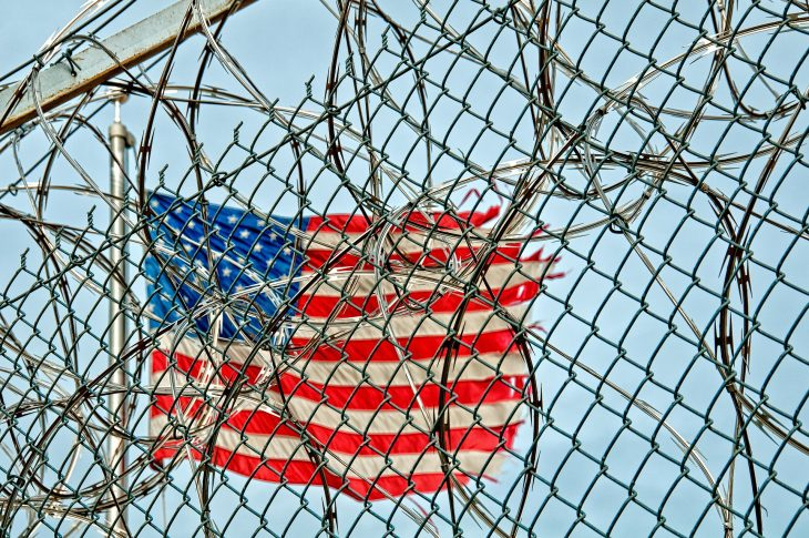 American flag behind razor-wire
