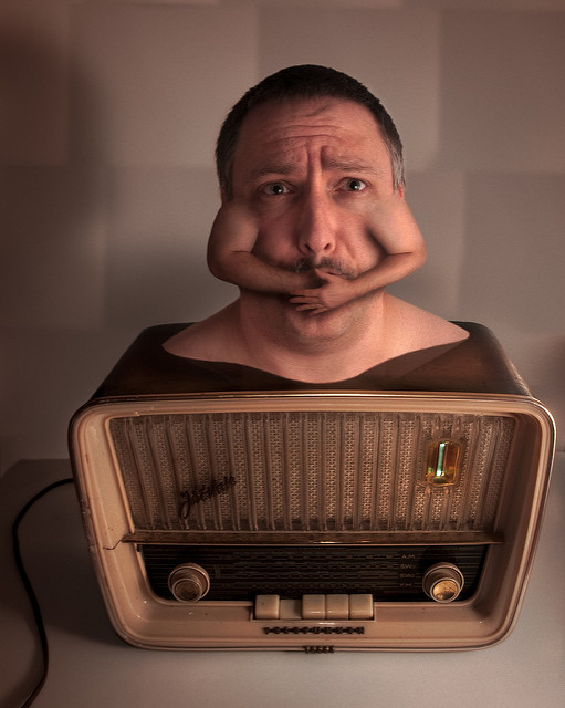 A surreal image of a man's head and shoulders rising out of a radio. His brows are drawn together in a look of concern and fear. Tiny arms sprout from where his ears should be, and their hands cover his mouth.