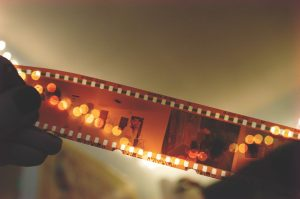 Strip of sepia-colored film held by two hands.