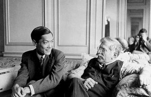 Magnus Hirschfeld and his student and lover Li Shiu Tong are seated on a couch in conversation.