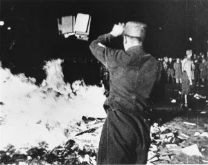 A Nazi throwing books on a bonfire in Berlin on May 10, 1933.