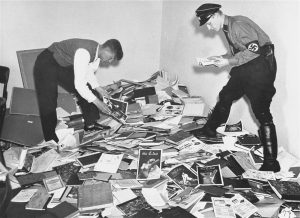 A student and a Nazi Stormtrooper rifle through a pile of items from the library of the Institute for Sexual Science.