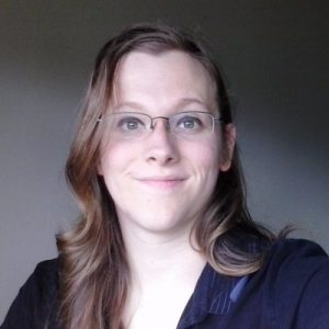 April Daniels, a woman with long hair and glasses, smiles at the camera.