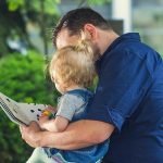 a father reads to his young child.