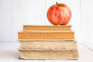 red apple atop a stack of books