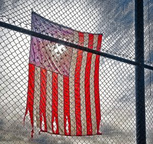 Ragged and slightly torn American flag hangs from a chain-link fence.