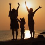 Two girls and a little girl with hands raised to meet the sunrise over the sea.  Focus on models. Shallow depth of field. Toned image.