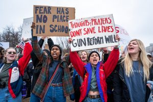 "several students from Parkland, Florida outside in a protest, holding signs ""Fear has no place in schools"" and ""Thoughts & prayers don't save lives. Gun reform will."""