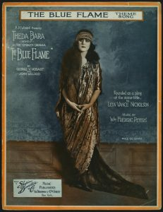 "Sheet music for the theme from ""The Blue Flame"" starring Theda Bara. Bara looks pensively to the left, in a heavy headband and long trailing brown dress, her back to a wall with blue wallpaper and brown wood below."