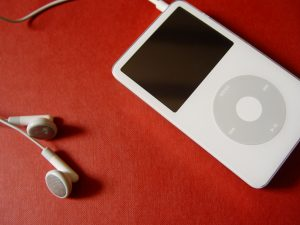 silver iPod Nano with earbuds plugged in on red background