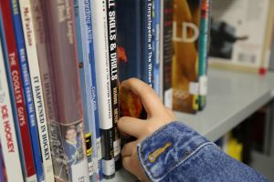 Someone's hand taking book off of library bookshelf.
