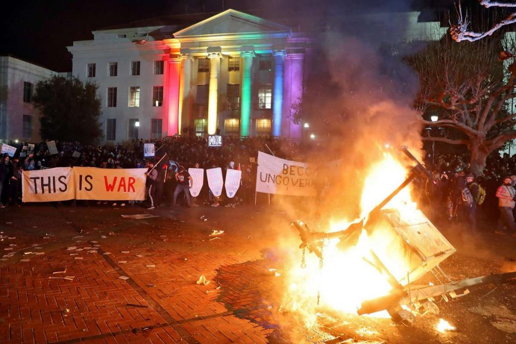 "Image credit: Scott Strazzante, The San Francisco Chronicle under Fair Use. Caption / alt text: A peaceful protest is disrupted by rioters that UC Berkeley university spokesperson Dan Mogulof describes as a ""paramilitary force."""