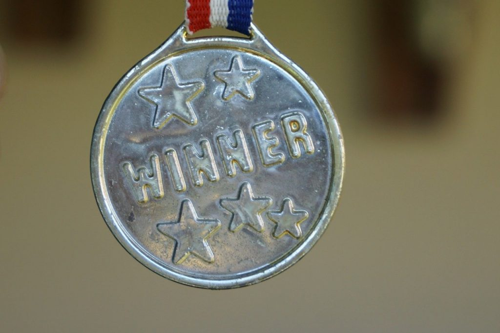 """Silver medal that says """"winner"""" suspended by red white and blue ribbon"""